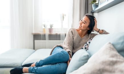 Young asian woman wearing her favorite jeans, lounging in her new Granite Loft apartment.