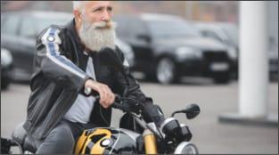 Mature gentleman returning to his Granite Lofts apartment, riding his motorcycle.