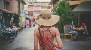 Woman in a large brim hat walking in an urban setting.