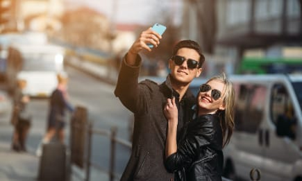Young millennial couple taking a selfie in front of their urban apartment.